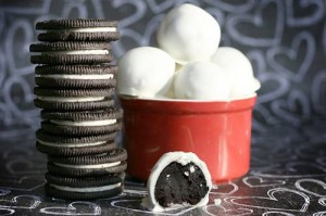 Picture of a stack of regular Oreo Cookies, plus a bowl full of the finished treats, including one that is missing a bite (which shows the inside).